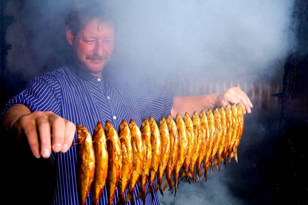 Schleswig-Holstein, Holsteinische Schweiz, Binnenfischerei auf dem Selenter See.Fischer beim räuchern von Silberfarbenen. Foto: Ingo Wandmacher